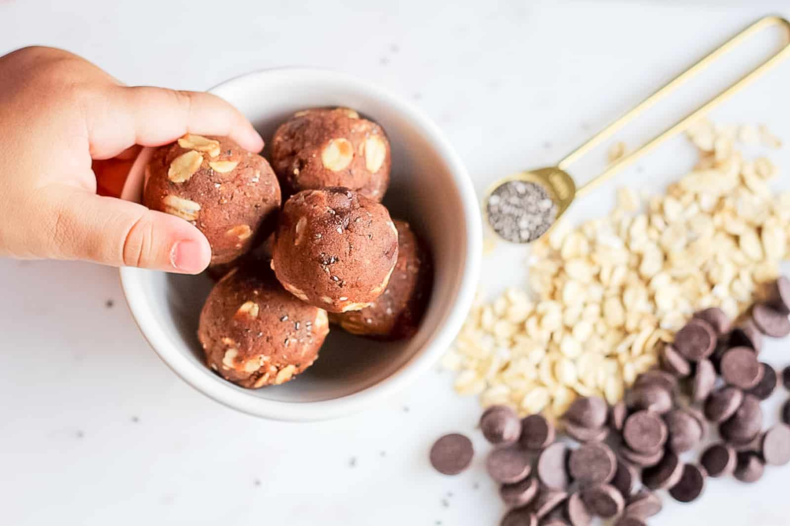 Almond Butter Energy Balls being picked up out of a white bowl with ingredients surrounding.