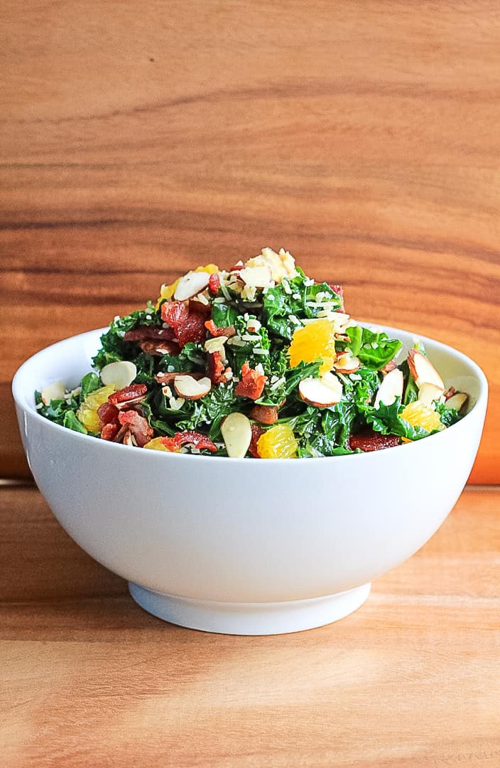 White bowl full of warm kale salad with bacon, oranges, parmesan and slivered almonds.