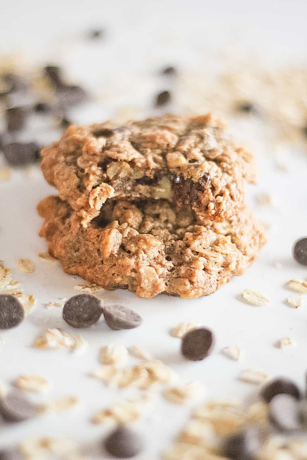Bite out of a cookie surrounded by oats and chocolate chips.