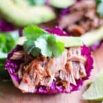 Final step is to serve the carnitas in a purple cabbage cup with avocado, cilantro and lime.