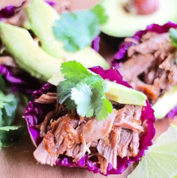 Serve the carnitas in a purple cabbage cup with avocado, cilantro and lime.
