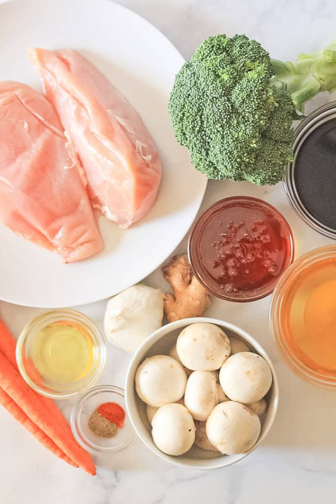 Ingredients for Instant Pot Teriyaki Chicken: raw chicken breast, broccoli, mushrooms, carrot, garlic, ginger, honey, apple cider vinegar and coconut aminos.
