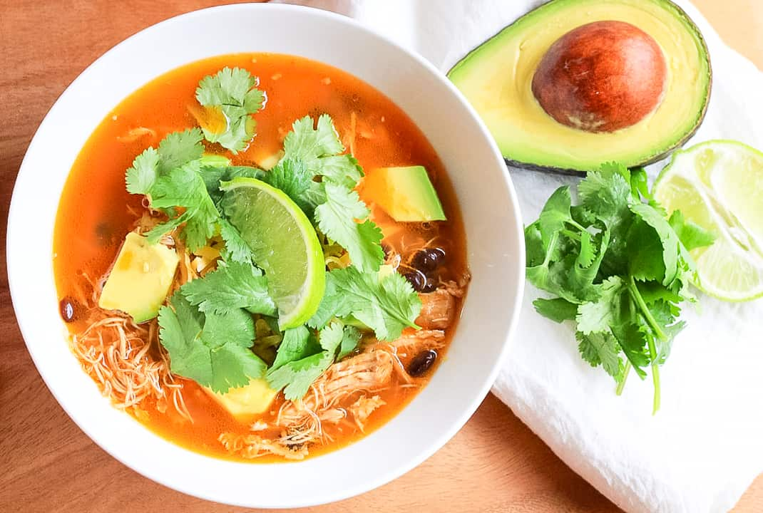 Instant pot chicken tortilla-soup in a white bowl with chunks of avocado, cilantro leaves and a lime wedge.