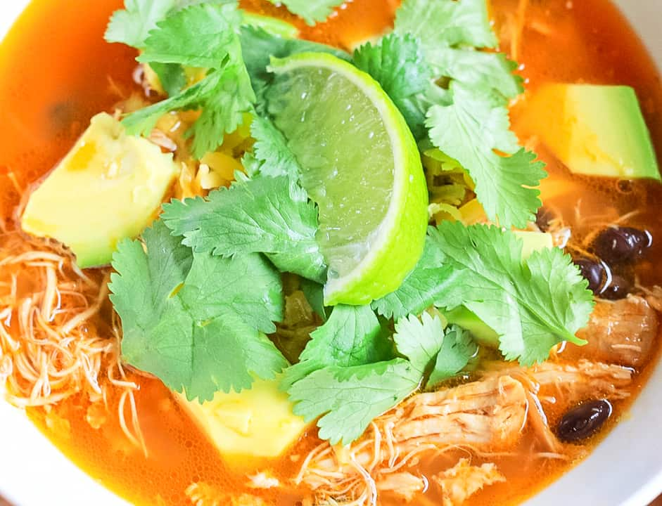 Close up of chicken tortilla-soup with chunks of avocado, cilantro leaves and a lime wedge.