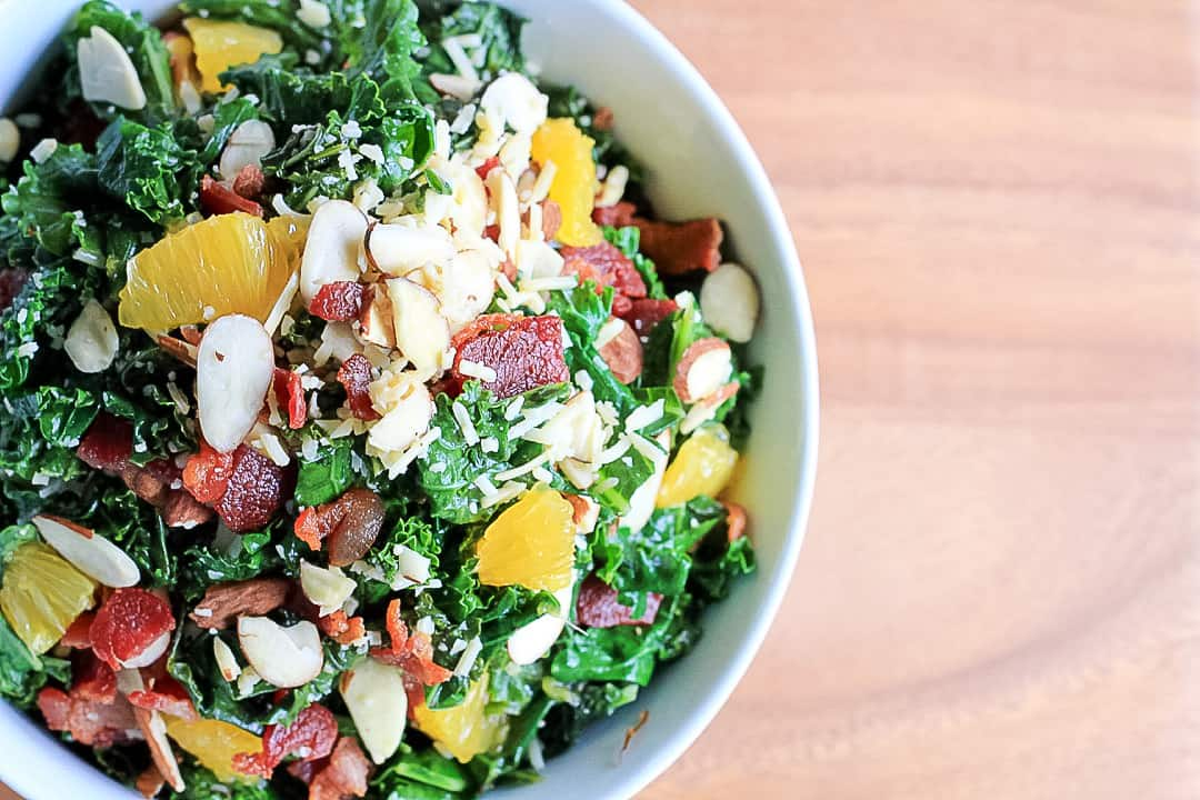 Top view of half a bowl of warm kale salad with bacon, oranges, parm and almonds.