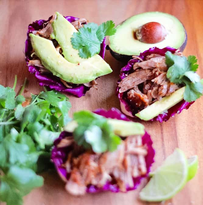 Whole30 Instant Pot Chipotle Pork Carnitas on a wood serving board in cabbage cups with avocado, lime and cilantro.