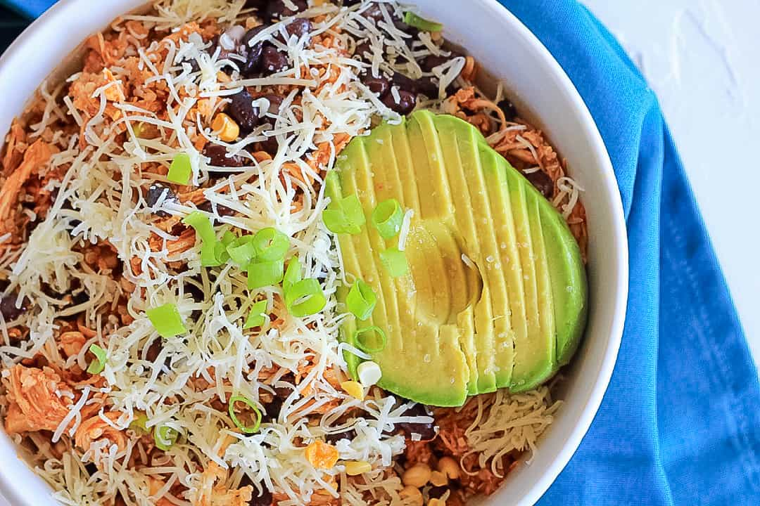 BBQ chicken salad in a white bowl topped with avocado, cheese and green onions.