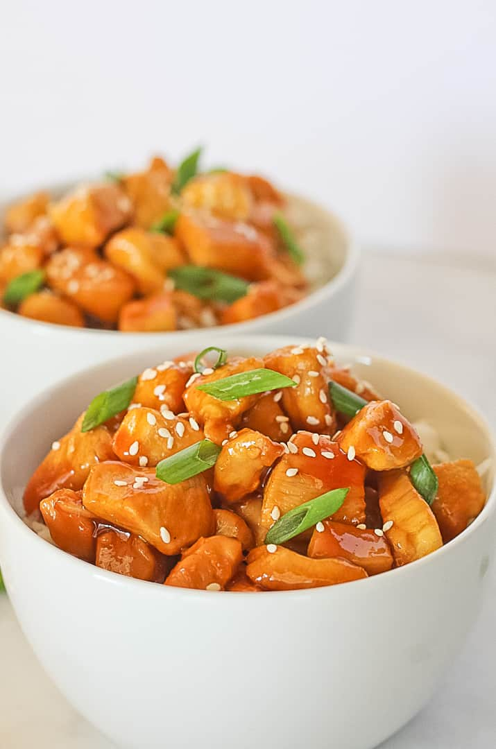 A white bowl of healthy orange chicken with green onions and sesame seeds.