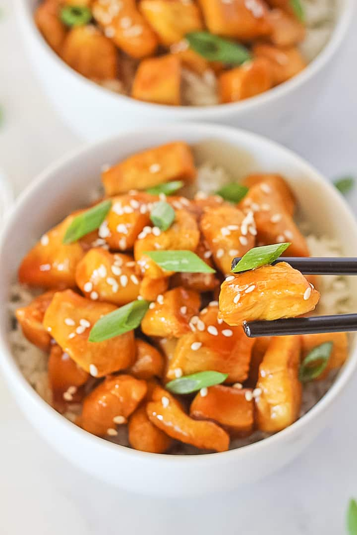 A white bowl of healthy orange chicken with green onions and sesame seeds with black chopsticks picking up a bite.