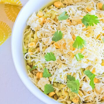 Close up of a white bowl filled with mexican street corn salad topped with cheese and cilantro.