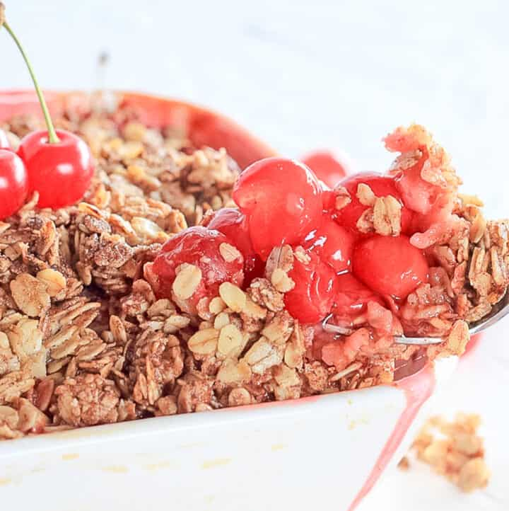 Scoop of pie cherries with crumble oat topping being taken from a white baking dish.