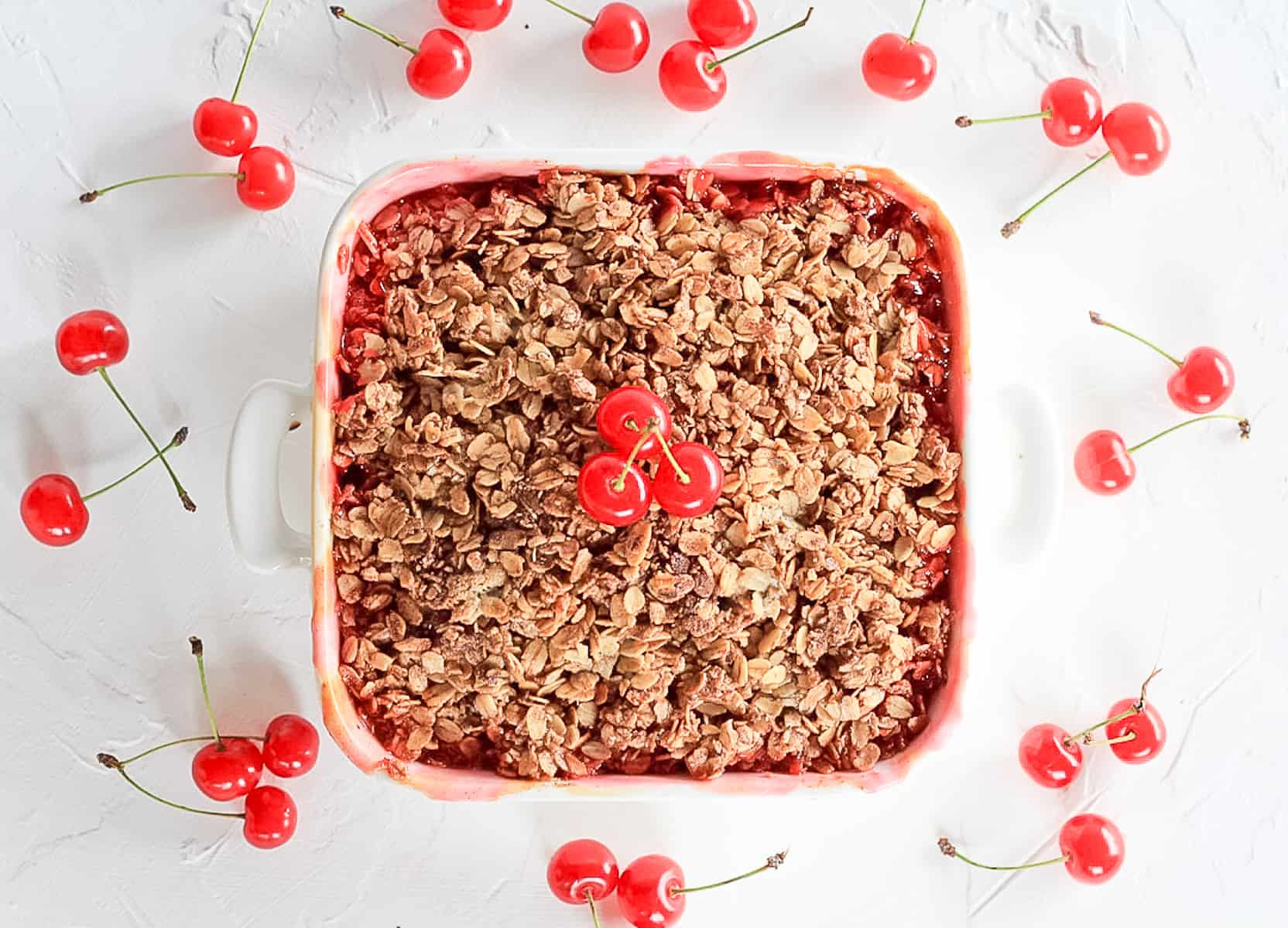 Overhead view of a square white baking dish filled with sour cherries and crisp oat topping.
