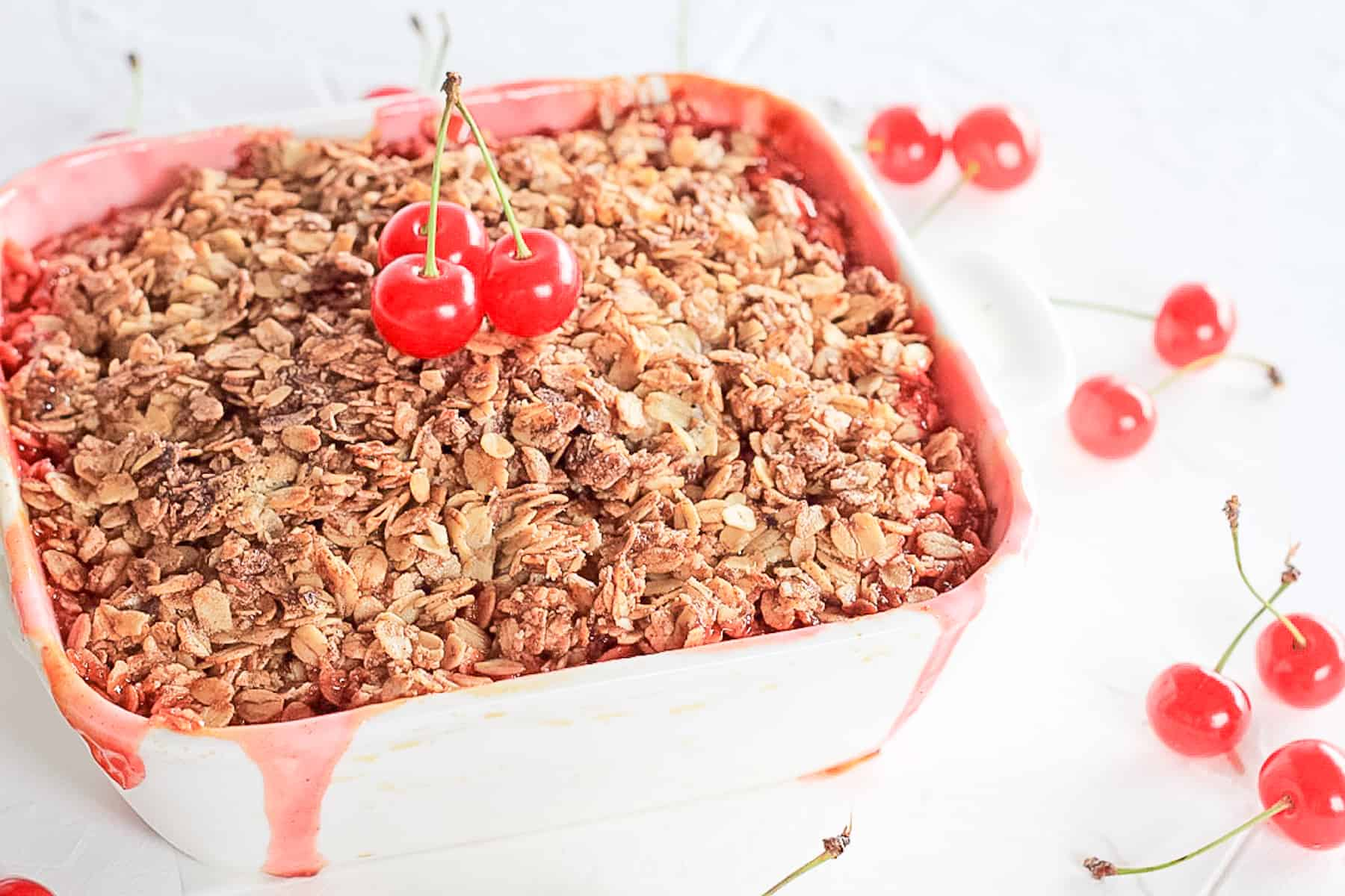 Side view of a cherry cobbler with cherry juice running down the side of the white baking dish.