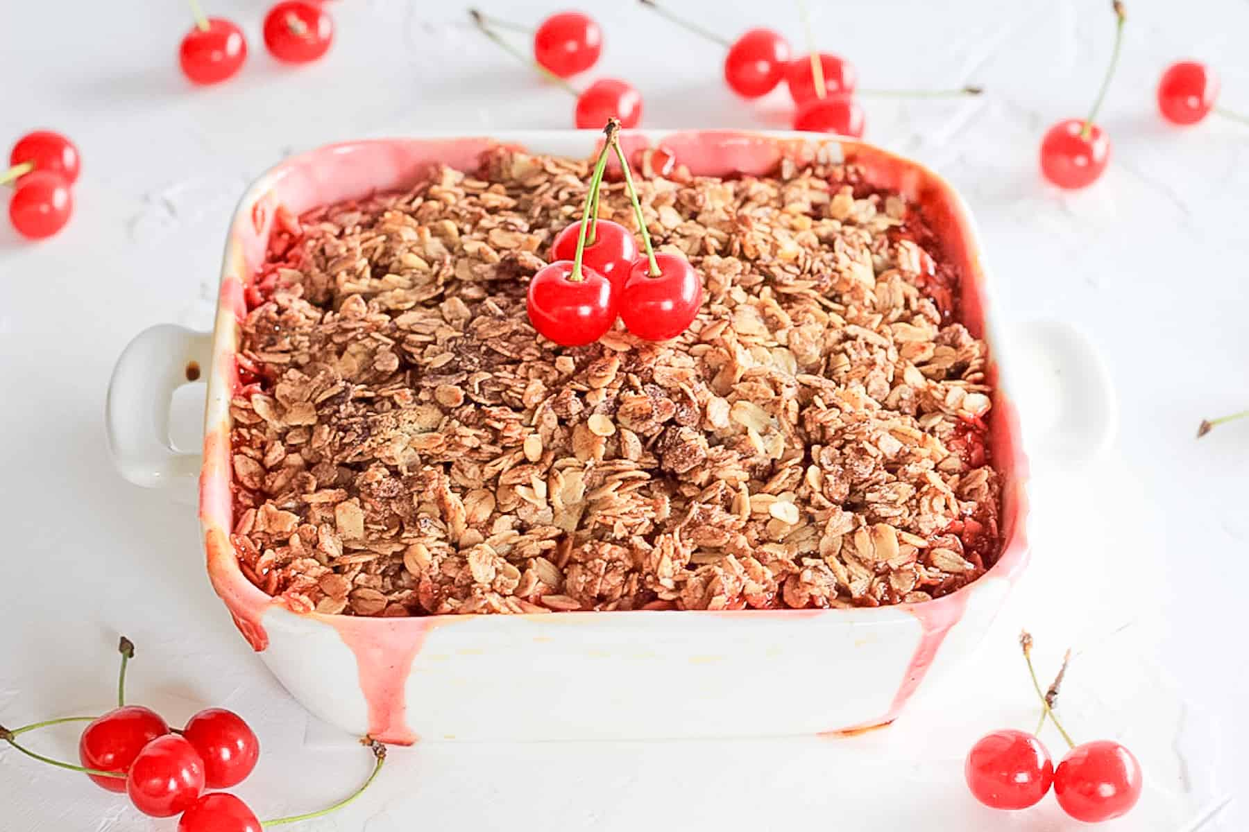Baking dish with cherry crumble surrounded by fresh cherries.