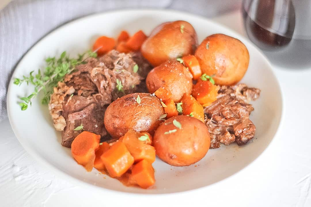 White plate of beef pot roast with whole baby potatoes and carrots and a thyme sprig with glass of red wine.