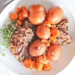 White plate of instant pot pot roast with whole baby potatoes and carrots and a thyme sprig.