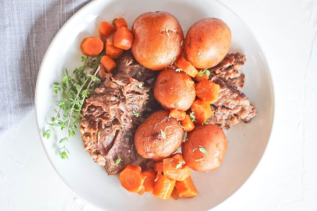White plate of beef pot roast with whole baby potatoes and carrots and a thyme sprig.