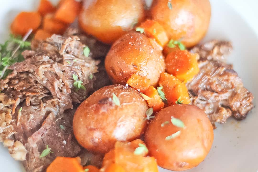 Close up of beef pot roast with whole baby potatoes and carrots.