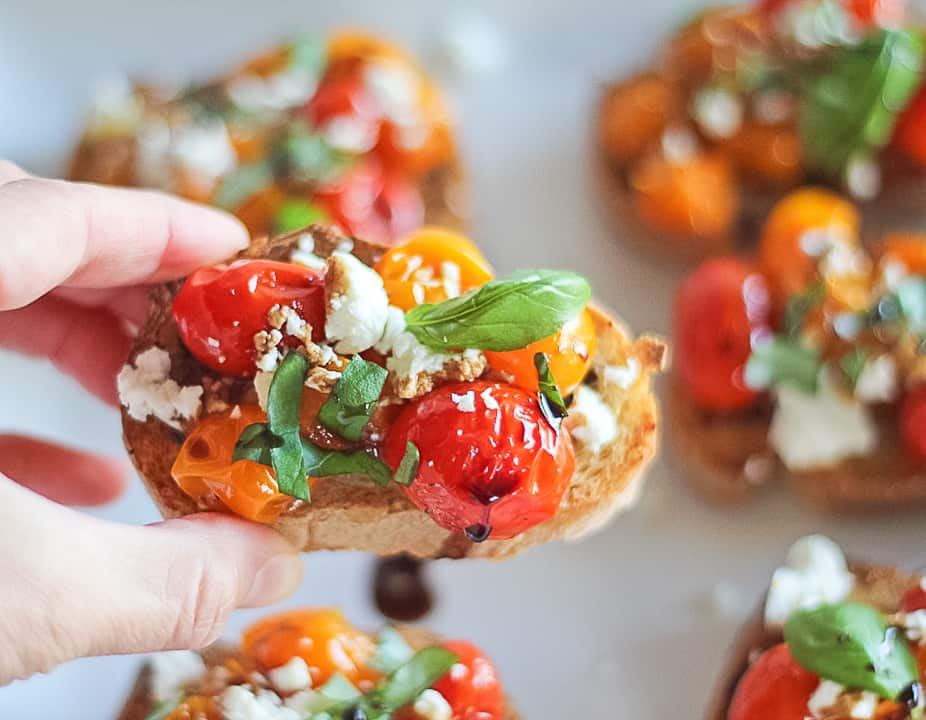 Hand picking up one cherry tomato crostini with goat cheese, basil and balsamic glaze on top.