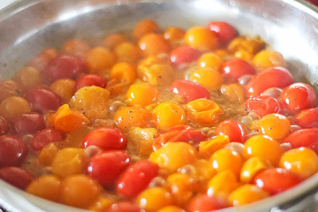 Stainless steel pan of bubbling yellow and red cherry tomatoes.