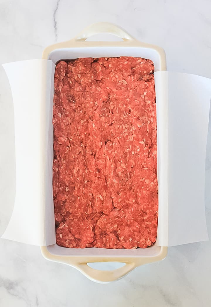 Uncooked Whole30 Meatloaf in a loaf pan lined with parchment paper.