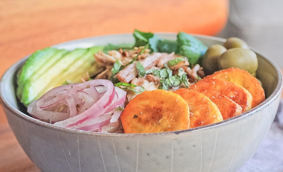 Side view of a bowl filled with cuban pork in the center and surrounded by green olives, cilantro, mint, avocado slices, pickled red onions and fried plantains.