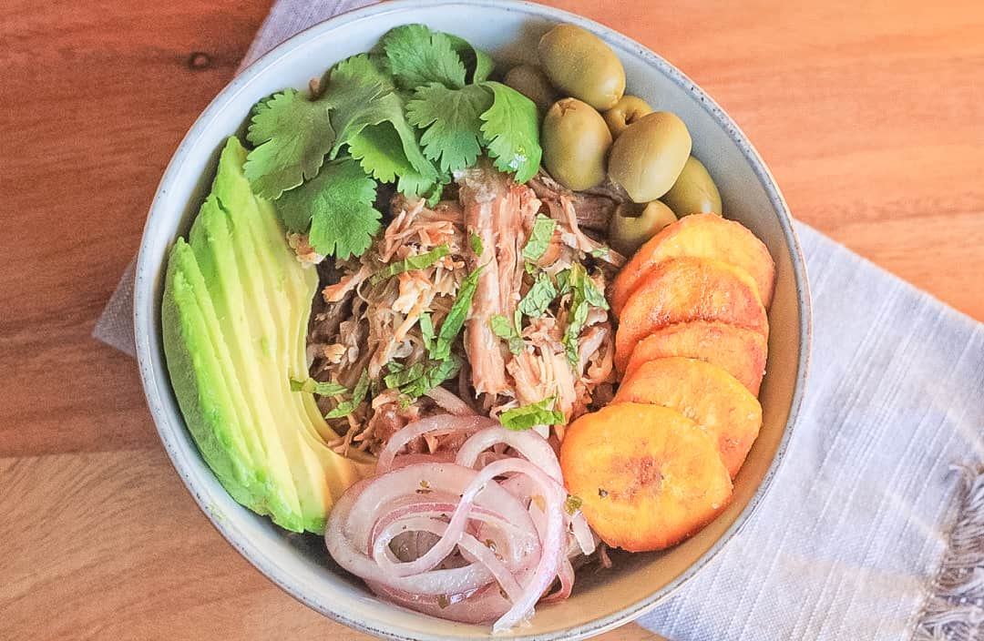 Overhead view of a bowl filled with cuban pork in the center and surrounded by green olives, cilantro, mint, avocado slices, pickled red onions and fried plantains.