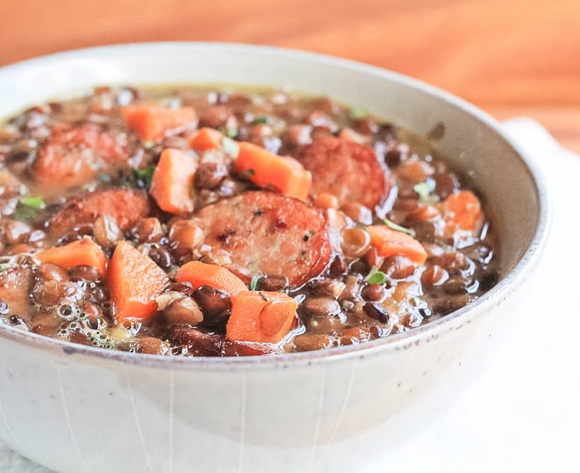 Lentil soup with smoked sausage in a bowl.