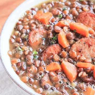 Close up of lentil soup with smoked sausage in a bowl.