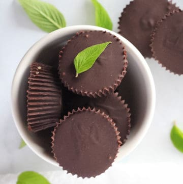 White bowl full of chocolate peppermint cups with mint leaves surrounding.