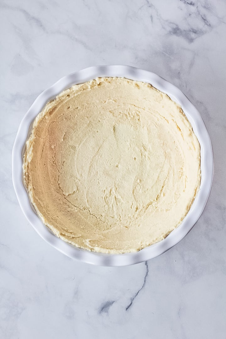 Par baked gluten free no roll pie crust in a white pie dish.