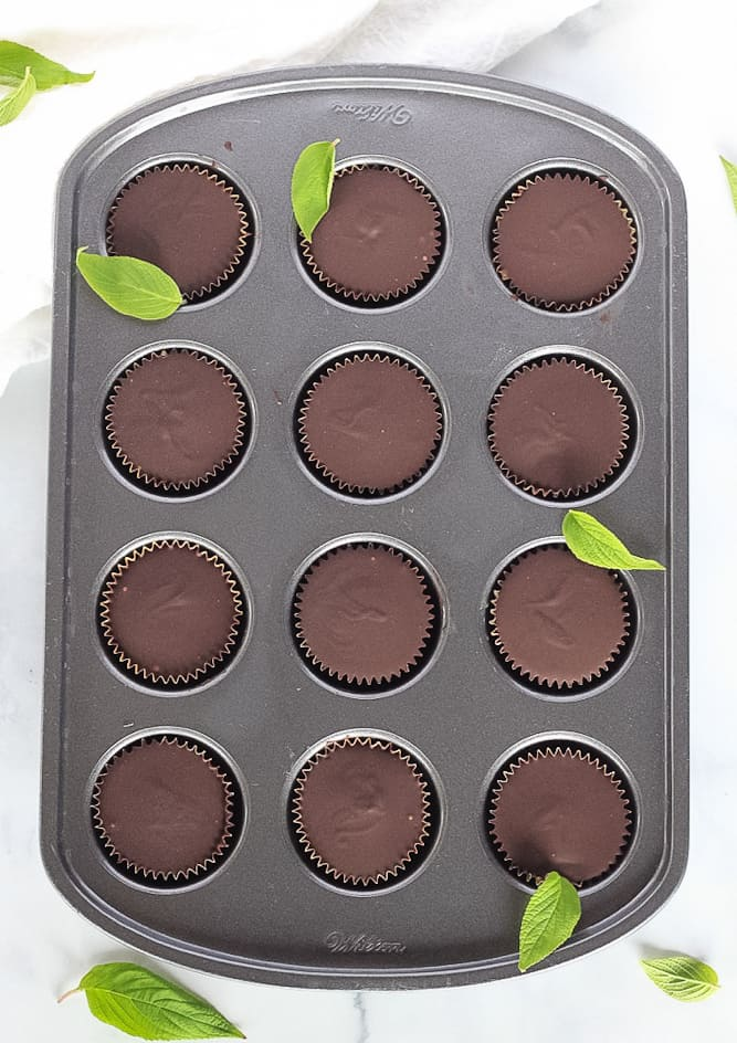 12 mini muffin pan filled with chocolate peppermint cups sprinkled with fresh mint leaves.