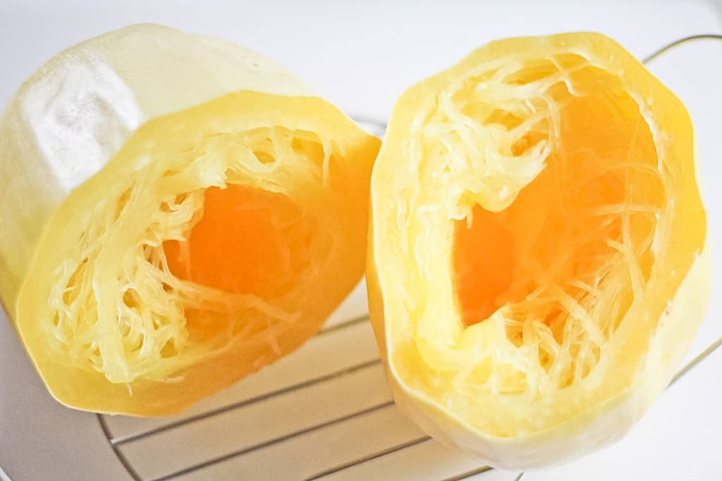 Two cooked halves of spaghetti squash cooling on the instant pot steamer basket.