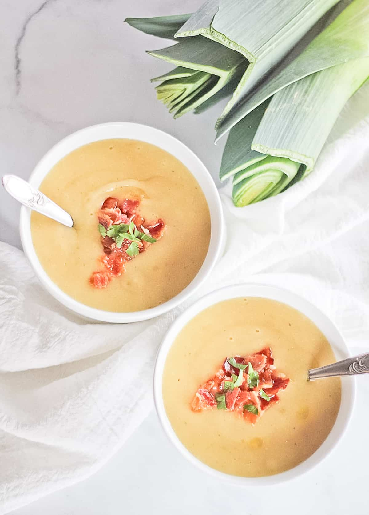 Two white bowls filled with soup topped with bacon.