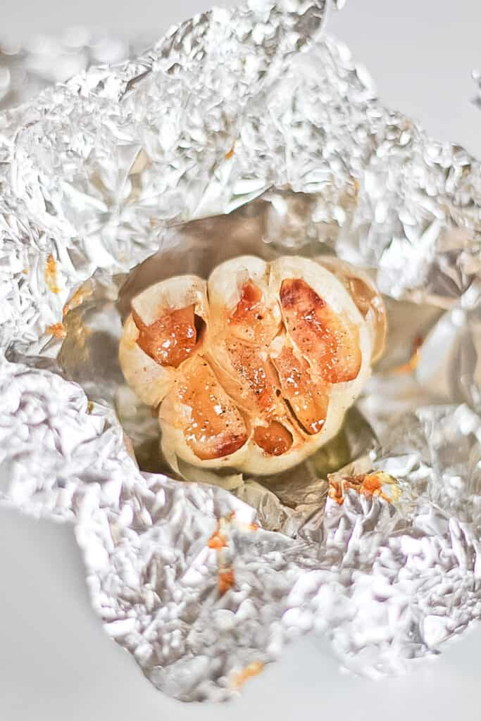 A head of roasted garlic sitting in foil.