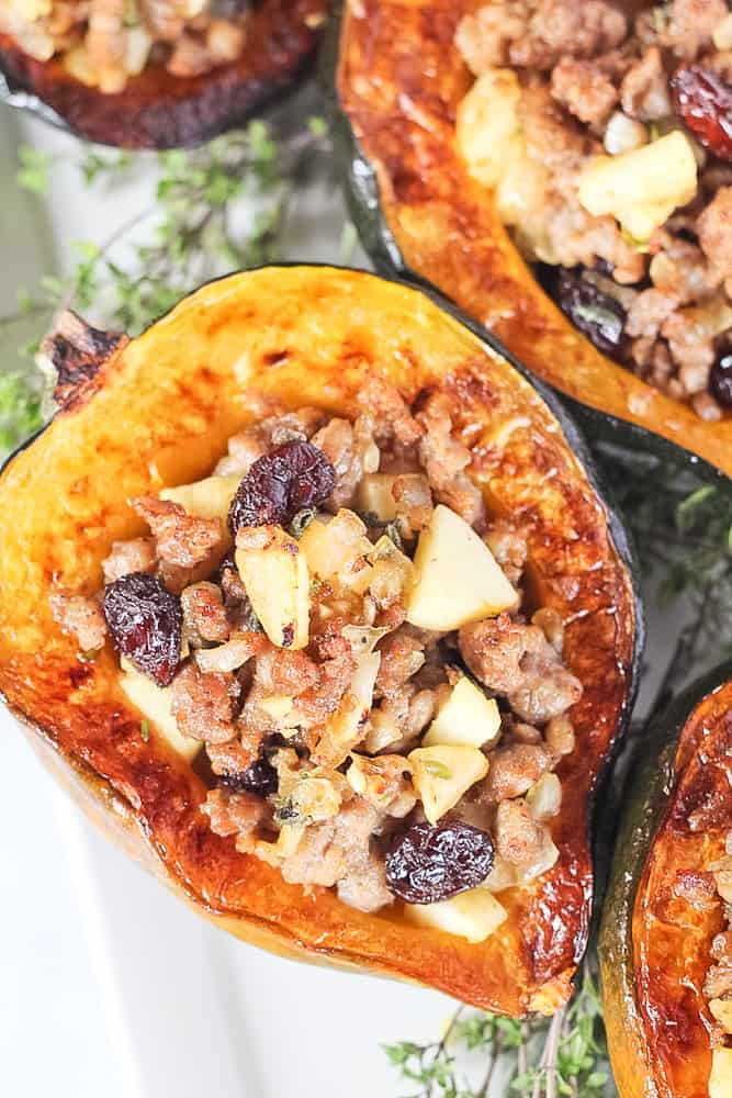 Stuffed acorn squash filled with sausage, apples and cranberries surrounded by herbs.