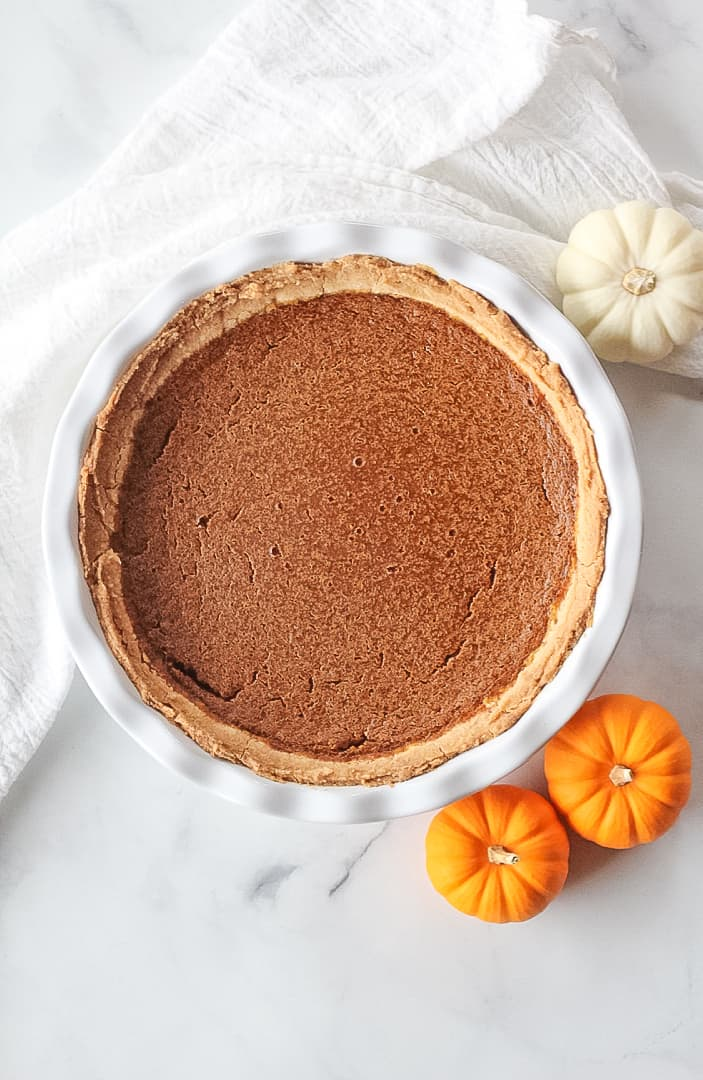 Whole Vegan Pumpkin Pie in a white pie dish with a white towel and three mini pumpkins surrounding.