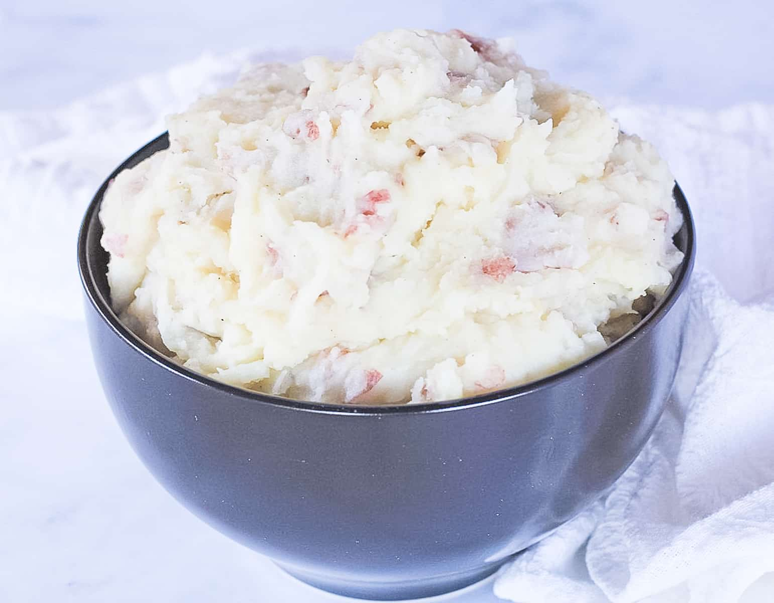Bowl of creamy mashed potatoes with skins.