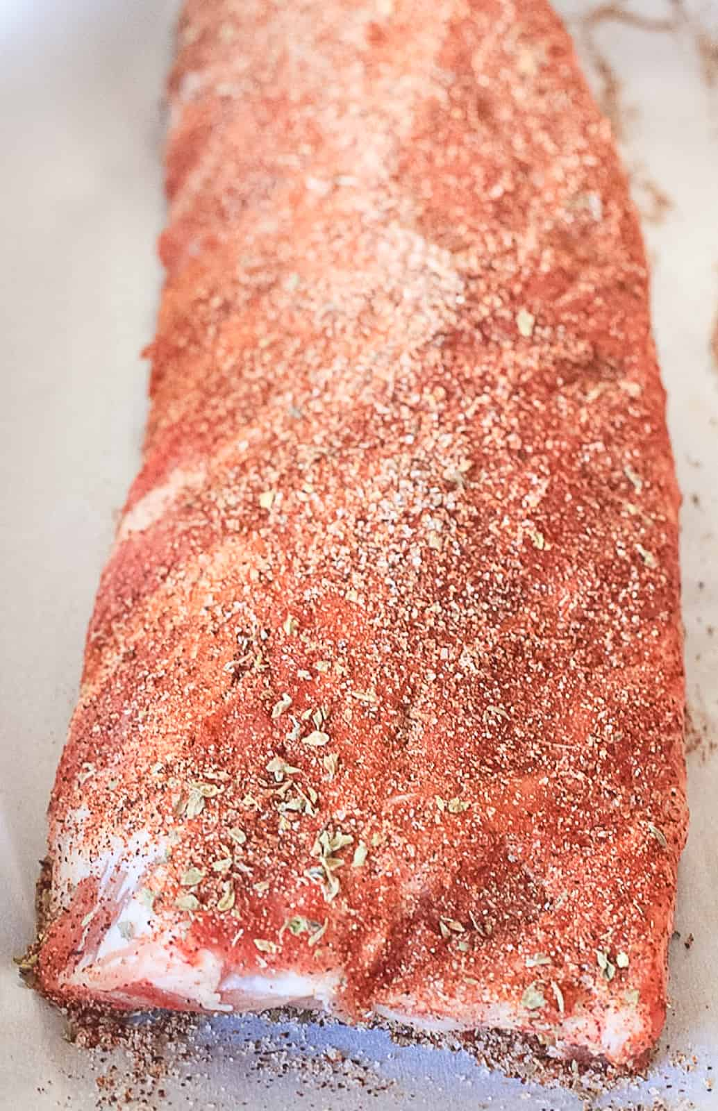Raw dry rubbed rack of ribs.