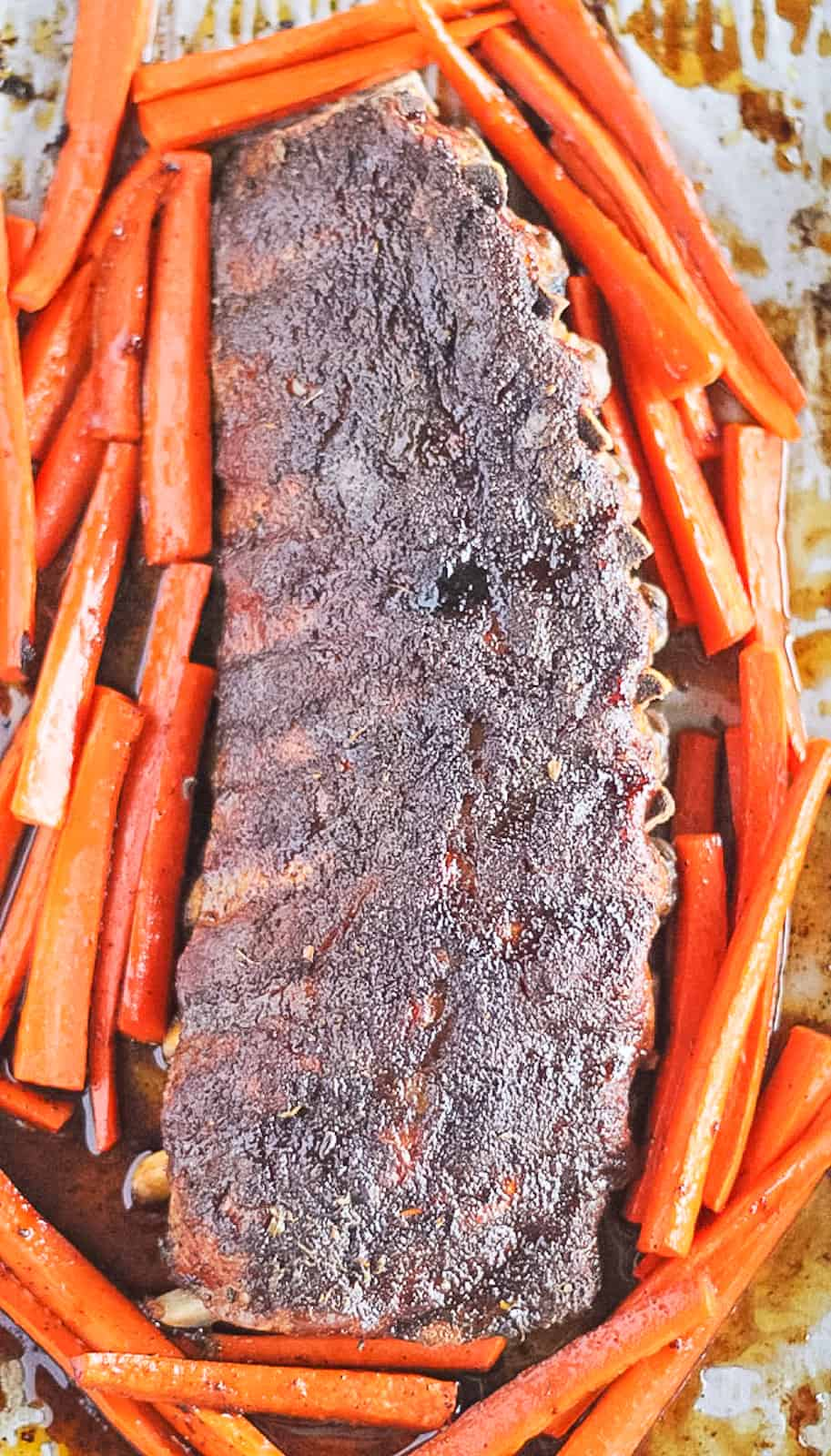 Dry rubbed caramelized rack of ribs on a sheet pan with carrots.