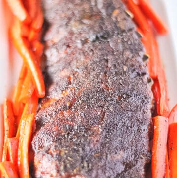 Baby Back Ribs in oven surrounded by caramelized carrots.