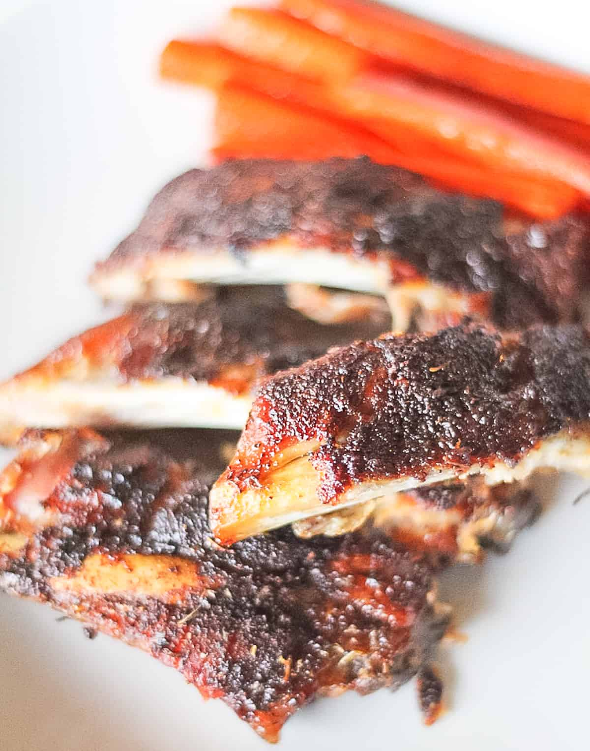 Sliced ribs on a plate with carrots.