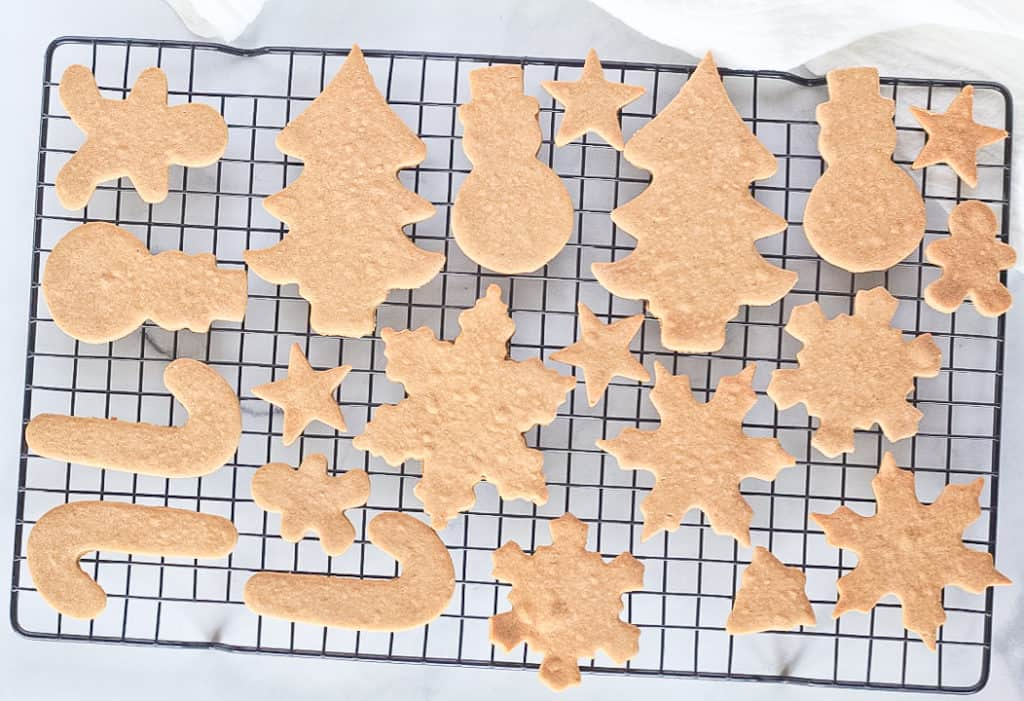 Cassava flour Christmas cut out sugar cookies cooling on a black wire rack.