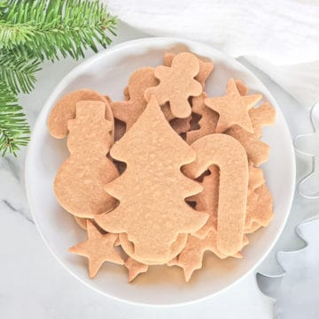 White plate of undecorated cassava flour sugar cut out cookies with cookie cutters and pine tree branch.