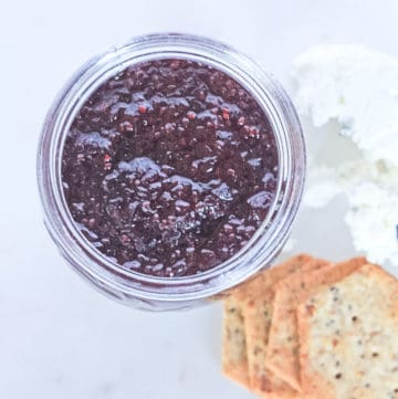 Looking into a mason jar to see blackberry chia seed jam surrounded by goat cheese and crackers.