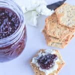 A jar of blackberry chia seed jam, goat's cheese on a knife and a cracker topped with goats cheese and chia seed jam.