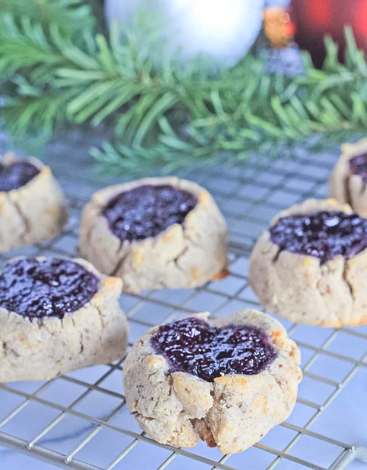 Paleo thumbprint cookies cooling on a wire rack filled with blackberry chia seed jam and pine branch in the back of the picture. .