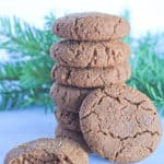 Stack of soft gingerbread cookies with with one laying next to it after a bite was taken and a pine branch in the background.