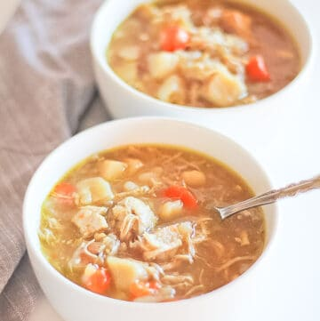 Two white bowls of Healthy Chicken Potato Soup with a spoon.