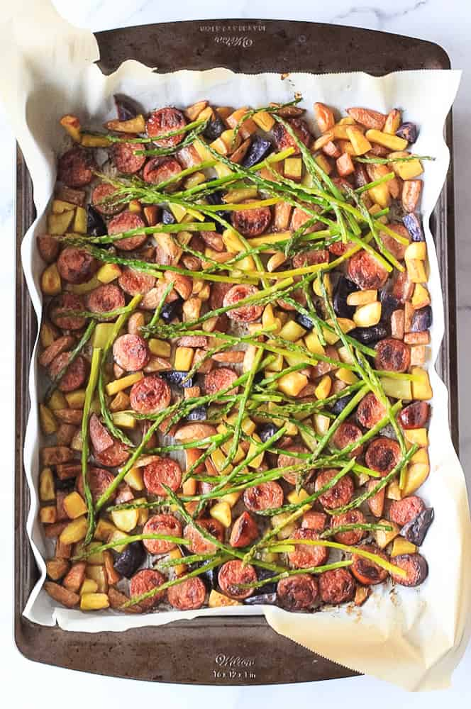 Sheet pan dinner of sausage, asparagus and crispy potatoes for an easy weeknight meal.